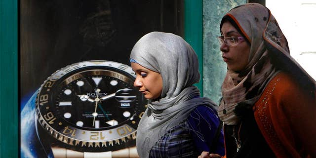 FILE - In this Monday, March 25, 2013 file photo, Egyptians walk in front of an advertisement for a watch in Cairo, Egypt. On midnight Thursday, Sept. 25, 2014, Egypt rolled back clocks one hour for the end of daylight savings time in the fourth time change in less than five months. Egypt is now two hours ahead of Greenwich Mean Time. In May the government moved clocks ahead one hour as a power-saving measure. It then switched clocks for the start and end of Ramadan, the Muslim fasting month, which this year fell in the scorching months of June and July. (AP Photo/Amr Nabil, File)