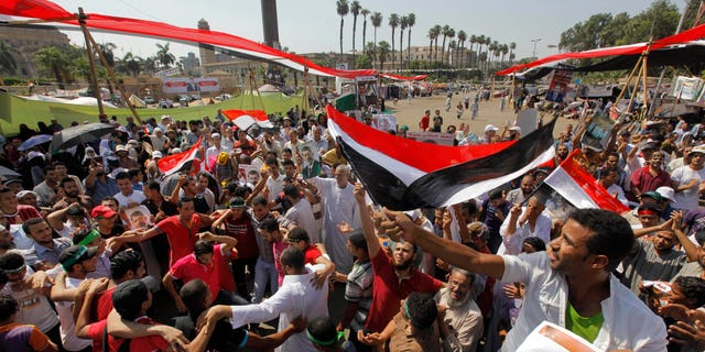 """Aug.2, 2013 - Supporters of Egypt's ousted President Mohammed Morsi shout slogans at a rally near Cairo University in Giza, Egypt. Arabic reads, """"to legitimacy."""""""