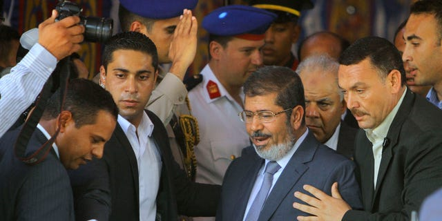 June 29, 2012: Egypt's President-elect Mohammed Morsi is guarded by presidential security as he leaves Friday prayers at Al-Azhar mosque, in Cairo, Egypt.