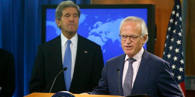 This July 29, 2013 file photo shows Secretary of State John Kerry listening as Martin Indyk speaks at the State Department in Washington.