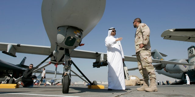 Nov. 12, 2007 - FILE photo of an Emarati visitor asks a U.S. military representative questions, as they stand next to an MQ-1 Predator spy plane, during the 2nd day of the 10th Dubai Airshow, at the Dubai airport, United Arab Emirates.