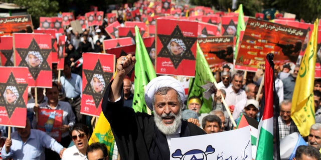 Aug. 2, 2013 - An Iranian cleric holding an anti-Israeli placard chants slogan, while attending an annual pro-Palestinian rally marking Al-Quds (Jerusalem) Day in Tehran, Iran. Thousands of Iranians marched in support of Muslim claims to the holy city of Jerusalem.