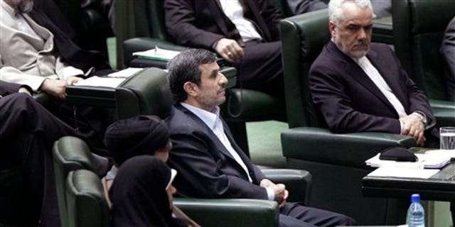 March 14: Iranian President Mahmoud Ahmadinejad, center, listens to conservative lawmaker Ali Motahari, unseen, a prominent opponent of the president, as he reads out a series of questions to Ahmadinejad in an open session in parliament in Tehran, Iran.