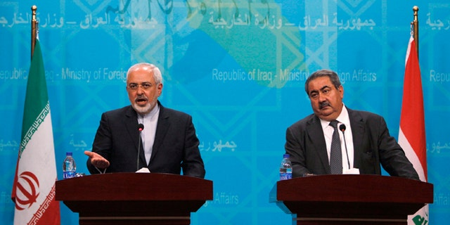 Iranian Foreign Minister Mohammad Javad Zarif, left, standing next to his Iraqi counterpart Hoshyar Zebari, speaks during a press conference in Baghdad, Iraq, Sunday, Aug. 24, 2014.