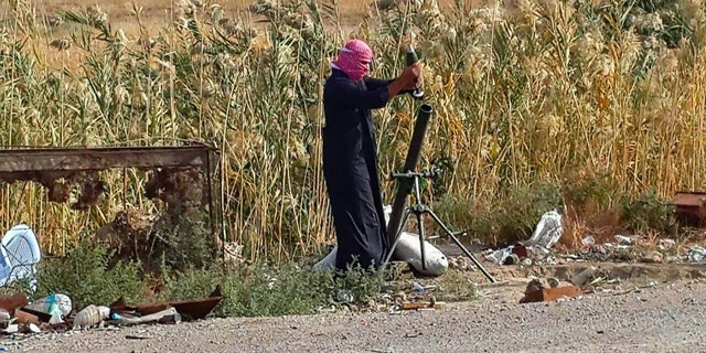 November 22, 2014: An Islamic State group fighter loads a mortar shell during clashes with Iraqi security forces in Ramadi, 70 miles west of Baghdad. (AP)