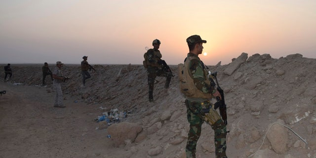 Oct. 15, 2015: Iraqi security forces and Sunni volunteer tribal fighters stand guard as the sun sets after clashes against ISIS.