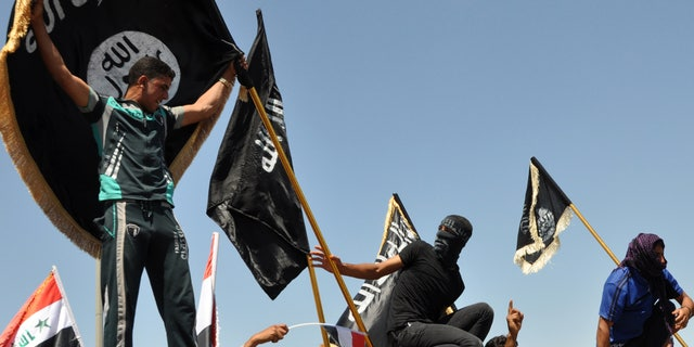 Masked Sunni protesters wave Islamist flags while others chant slogans at an anti-government rally in Fallujah, Iraq, April 26, 2013. The leader of Al Qaeda's Iraq arm, Abu Bakr al-Baghdadi, defiantly rejected an order from the terror network's global command to scrap a merger with the organization's Syria affiliate, according to a message purporting to be from Al-Baghdadi that was posted online  June 15, 2013.