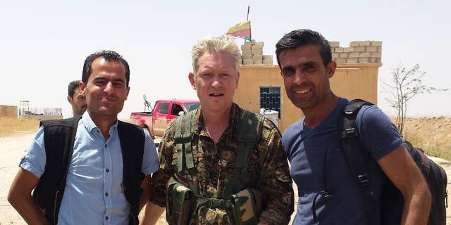 """In this handout photo provided by Kurdish journalist Mohammed Hassan, taken on May 19, 2015, Michael Enright, center, a British actor who has had minor roles in Hollywood films, wears the Kurdish fighters military uniform after he joined them battling against the Islamic State group, near Tel Tamr town, northeast Syria. Enright, who played a deckhand in """"Pirates of the Caribbean: Dead Man's Chest,"""" appears in a video released by the Kurdish People's Protection Units, known as the YPG. The video shows him in a trench with other fighters firing an assault rifle."""
