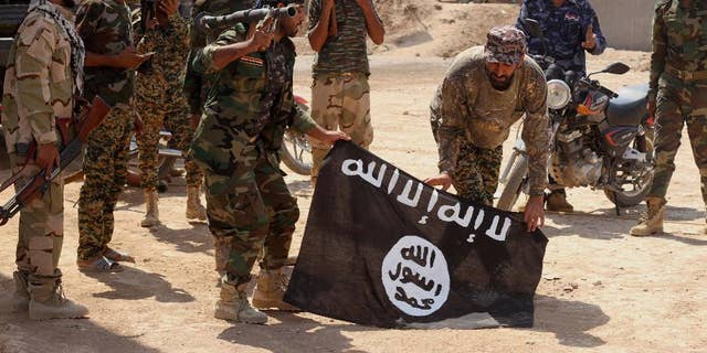 FILE - In this Tuesday, Oct . 7, 2014 file photo, Iraqi security forces hold a flag of the Islamic State group they captured during an operation outside Amirli, some 105 miles (170 kilometers) north of Baghdad, Iraq. The mass beheadings of Egyptian Christians by militants in Libya linked to the Islamic State group have thrown a spotlight on the threat the extremists pose beyond their heartland in Syria and Iraq, where they have established a self-declared proto-state. Militants in several countries have pledged allegiance to IS leader Abu Bakr al-Baghdadi. (AP Photo, File)