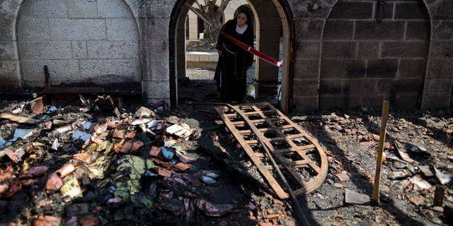 A nun looks at damage to the Church of the Multiplication of the Loaves and Fish in June 2015.