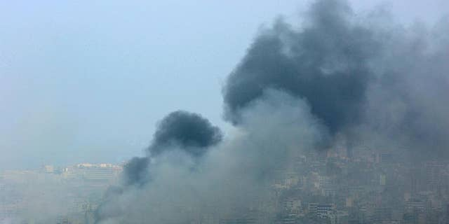 FILE - In this Sunday July 16, 2006 file photo, black smoke rises from the demolished headquarters of Hezbollah in the suburbs of Beirut, Lebanon, following Israeli air strikes. Hezbollah is building up a massive arsenal of rockets and other advanced weaponry in an arms race that may lead to a new war between Israeli and the militant Lebanese group, a senior Israeli military intelligence official said Wednesday, May 13, 2015. (AP Photo/Kevork Djansezian, File)