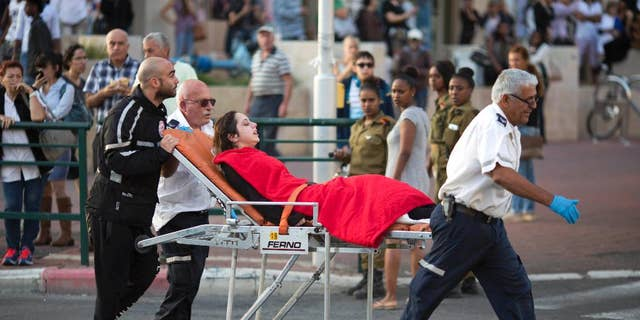 FILE - In this Monday, Nov. 2, 2015 file photo, Israeli rescue personal evacuate a woman after a stabbing attack in Rishon Lezion, Israel. After years of relative quiet in major Israeli cities, a seven-week burst of violence has brought the Palestinian issue back to the country's heartland and pushed the long-festering issue onto the national agenda. (AP Photo/Ariel Schalit, File)