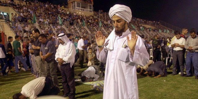 FILE - In this  Friday, Sept. 14, 2001 file photo, an Israeli Arab prays alongside other Muslims during a rally of the Islamic movement in the Arab Israeli town of Um El-Fahem. (AP Photo/Elizabeth Dalziel, File)