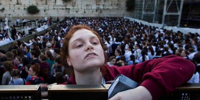 "A Jewish orthodox woman follows a prayer organized by the ""Women of the Wall"" organization."