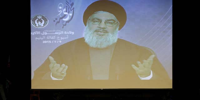 Hezbollah leader Sheikh Hassan Nasrallah speaks via video to his supporters in the southern suburb of Beirut, Lebanon, Friday Jan. 9, 2015. The leader of the Lebanese Hezbollah group said Islamic extremists have insulted the prophet of Islam with their terror more than those who published drawings mocking him. (AP Photo/Hussein Malla)