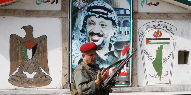 "A member of the Palestine Liberation Organization's Armed Struggle unit, that is in charge of security in the Palestinian camps, holds his AK-47 machine gun as he walks in front of a portrait of the late Palestinian leader, Yasser Arafat, at a checkpoint in the Palestinian refugee camp of Ein el-Hilweh, in Sidon, Lebanon, Tuesday June 19, 2012. Palestinians refugees are protesting after clashes broke out Monday in the Nahr el-Bared camp in the north of Lebanon during the funeral of a Palestinian who was killed in a confrontation Friday. The Arabic logo painted on the wall, right, reads ""The Palestine Liberation Organization, national unity, liberation."" (AP Photo/Mohammed Zaatari)"