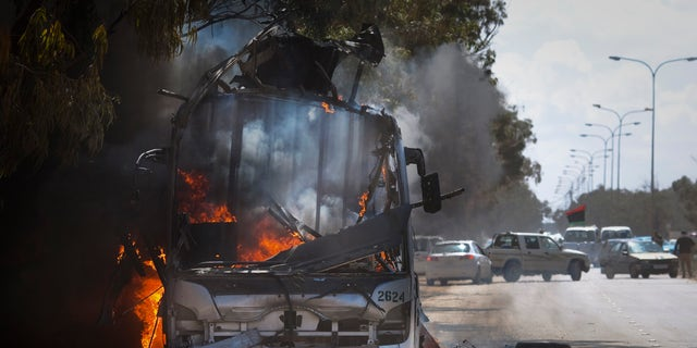 Sunday: A bus burns on a road leading to the outskirts of Benghazi, eastern Libya.