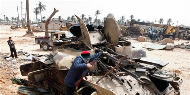 April 22: A Libyan rebel fighter climbs on  a destroyed government armored vehicle in the besieged city of Misrata, the main rebel holdout in Qaddafi's territory. (AP)