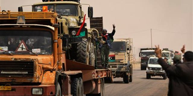 April 7: Libyan rebel fighters with vehicle-mounted multiple rocket launchers loaded on flatbed trucks head to the front line, from the western gate of Ajdabiya, Libya. Rebel fighters claimed NATO airstrikes blasted their forces Thursday in another apparent mistake that sharply escalated anger about coordination with the military alliance in efforts to cripple pro-Gadhafi forces. (AP)