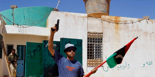 A Libya fighter celebrates as revolutionary fighters enter a Muammar Qaddafi political office next to a police station as they take control of Qaddafi loyalists villages in the desert some 730 km south of Tripoli, at Mahruga, 50 kms north of the southern city of Sebbah, Libya, Saturday, Sept. 17, 2011.