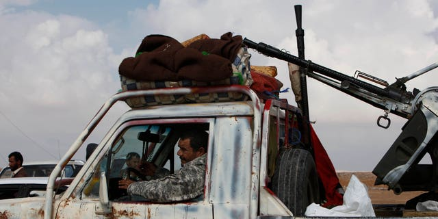 A Libyan rebel passes through the western gate of Ajdabiya, Libya on Friday, April 1, 2011. The western gate is closed for journalists and civilians trying to reach the front line of the conflict in Libya.