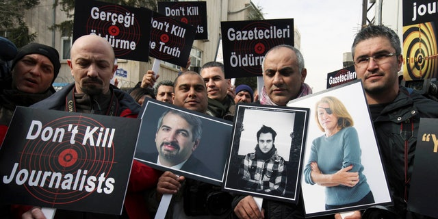 Feb. 24, 2012: In this file photo,Turkish journalists holding photographs of their colleagues who lost their lives in Syria recently, from left, Anthony Shadid, Remi Ochlik and Marie Colvin, stage a protest outside the Syrian Embassy in Ankara.