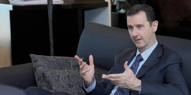 """FILE - In this Monday, Aug. 26, 2013 file photo released by the Syrian official news agency SANA, Syrian President Bashar Assad gestures as he speaks during an interview with a Russian newspaper in Damascus, Syria. Assad said Thursday, March 6, 2014, that Russia's military takeover of Crimea reflects President Vladimir Putin's """"wise policy"""" and his efforts to restore """"security and stability"""" in Ukraine after an """"attempted coup."""" (AP Photo/SANA, File)"""