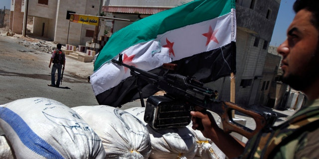 FILE: June 10, 2012: A Free Syrian Army solider aims his weapon at a checkpoint in the northern town of Ariha, on the outskirts of Idlib, Syria.