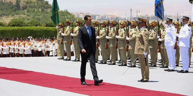 In this photo released by the Syrian official news agency SANA, Syria's President Bashar Assad reviews an honor guard upon his arrival at the presidential palace to take the oath of office for his third seven-year term in Damascus, Syria, Wednesday, July 16, 2014.