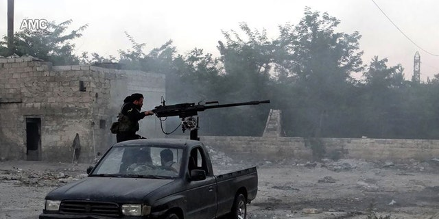 June 20, 2013 - Syrian rebel fires a heavy machine gun towards Syrian soldiers loyal to Syrian President Bashar Assad in Aleppo, Syria.  (Citizen journalism image provided by Aleppo Media Center.)