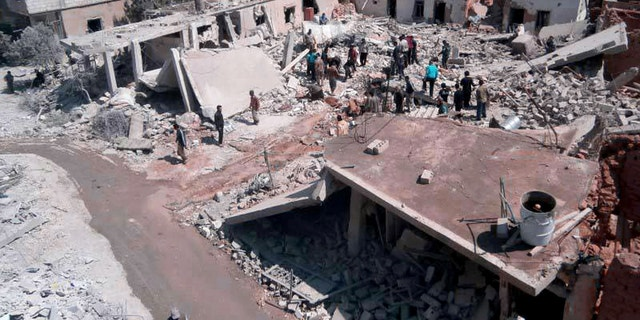 May 21, 2013 - FILE citizen journalism image provided by Qusair Lens, shows Syrian citizens gathering over houses that were destroyed by a Syrian forces air strike in the town of Qusair, near the Lebanon border.