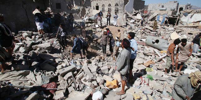 People search for survivors under the rubble of houses destroyed by Saudi-led airstrikes in Sanaa, Yemen, Friday, May 1, 2015. Saudi Arabia leads a coalition of mostly Sunni Arab countries conducting airstrikes against the rebels who have overrun the Yemeni capital, Sanaa, and forced the Western-backed president, Abed Rabbo Mansour Hadi, to flee the country.  (AP Photo/Hani Mohammed)