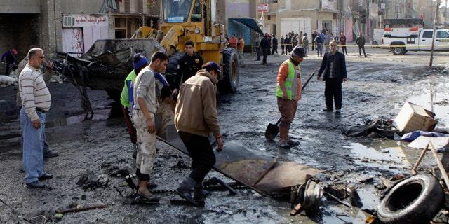 Jan. 27: People clean the scene of a car bomb attack in Zafaraniyah, Baghdad.