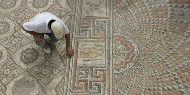 An unidentified man examines part of a mosaic, measureing around 9,700 square feet (900 square meters), in ruins of an 8th-century Islamic palace outside the West bank town of Jericho, Sunday, Oct. 10, 2010.