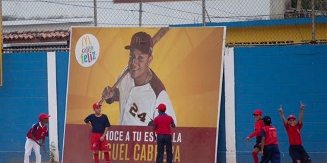 Two boys stand in front of an advertisement featuring Miguel Cabrera during a baseball practice in Maracay.