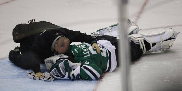 Dallas Stars goalie Kari Lehtonen (32) is tended to after being hit by Minnesota Wild left wing Erik Haula (56) at American Airlines Center in Dallas March 8, 2014. (AP Photo/The Dallas Morning News, Nathan Hunsinger