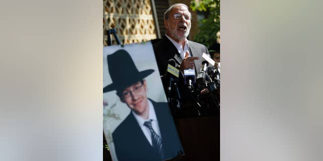 Then-New York assemblyman Dov Hikind standing near a photograph of Aaron Sofer, in Lakewood, N.J., in 2014. Sofer, missing at the time, later was found dead.