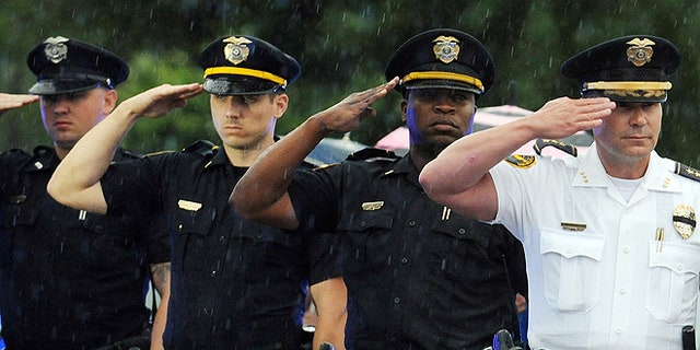 Hattiesburg police officers salute their fallen fellow officer Benjamin Deen as the hearse carrying his body arrives at the Hulett Winstead Funeral Home in Hattiesburg, Miss., Monday, May 11, 2015. Officers Deen and Liquori Tate were gunned down Saturday night during a traffic stop near the East 4th and Bouie Street intersection. (Photo by Ryan Moore/WDAM-TV via AP)