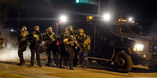 FILE: Aug. 18, 2014: Police in suburban St. Louis after the shooting of Michael Brown by a police officer started rancorous protests in Ferguson, Mo.