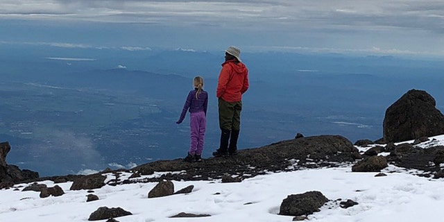Montannah and their tour guide reflect at the top of the mountain.
