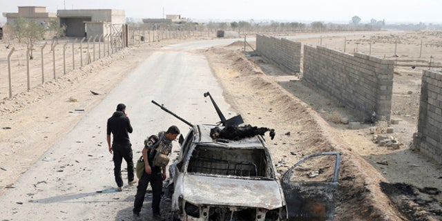 Iraqi Special Forces soldiers looks at a destroyed Islamic State vehicle in a village near Mosul, Iraq.
