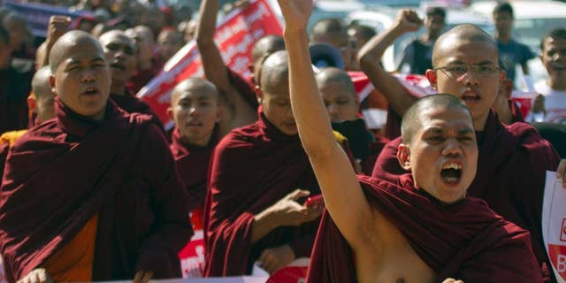Myanmar Buddhist monks shout slogans as they march to protest against a resolution adopted by the UN General Assembly calling on Myanmar to grant citizenship to Rohingya, Friday, Jan.16, 2015, in Yangon, Myanmar. The United Nations General Assembly's human rights committee passed a resolution last year, urging Myanmar to grant citizenship to the Rohingya, a stateless Muslim minority group. (AP Photo/Khin Maung Win)