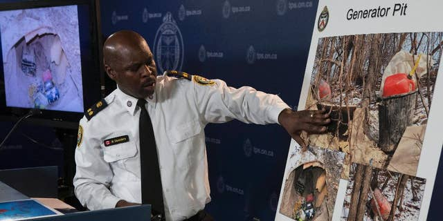 In a Tuesday, Feb. 24, 2015 photo, Toronto's Deputy Police Chief Mark Saunders explains evidence photos as he speaks to the media about a tunnel found near one of the venues for this year's Pan American Games, at a press conference in Toronto. Police said Monday March 2, 2015 that two young men who built the mysterious tunnel had no criminal intent, they just wanted a man cave. Const. Victor Kwong said tips from the public helped them identify the two men in their 20s responsible for building the underground chamber near a Pan Am Games venue. (AP Photo/The Canadian Press, Chris Young)