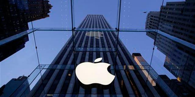 In this Sept. 5, 2014 file photo, the Apple logo hangs in the glass box entrance to the company's Fifth Avenue store, in New York.