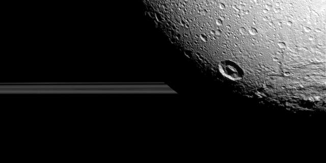Saturn's moon Dione hangs in front of Saturn's rings in this view taken by NASA's Cassini spacecraft during the inbound leg of its last close flyby of the icy moon.