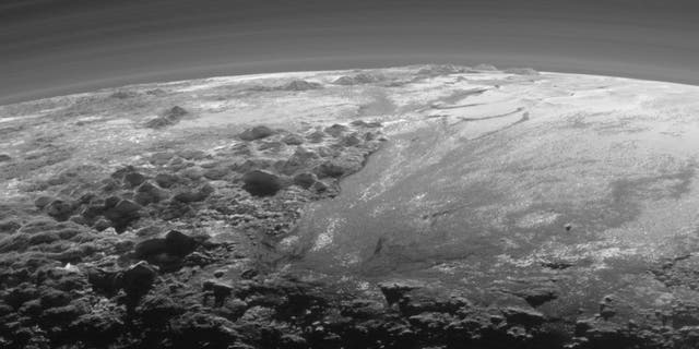The smooth expanse of the informally named Sputnik Planum (right) is flanked to the west (left) by rugged mountains up to 11,000 feet high, including the informally named Norgay Montes in the foreground and Hillary Montes on the skyline. The backlighting highlights more than a dozen layers of haze in Pluto's tenuous but distended atmosphere. The image was taken from a distance of 11,000 milesto Pluto; the scene is 230 miles across.