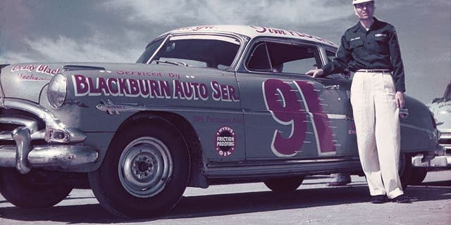 DAYTONA BEACH, FL - FEBRUARY 1952: Tim Flock poses with the Ted Chester-owned Blackburn Auto Service Hudson Hornet before NASCAR Cup racing activity on the Daytona Beach-Road Course. Flock drove for Chester from 1951 through 1953, winning 10 races and the 1952 Cup championship. (Photo by ISC Images & Archives via Getty Images)
