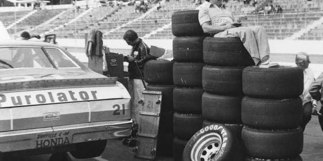 """MARTINSVILLE, VA — 1980: Driver Neil Bonnett uses a stack of Goodyear tires as a makeshift """"easy chair"""" as he watches practice for a NASCAR Cup race at Martinsville Speedway. (Photo by ISC Images & Archives via Getty Images)"""