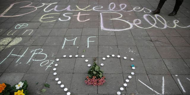 """A message written on the ground reads """"Brussels is beautiful"""" next to flowers and candles following attacks in Brussels on March 22, 2016. Airlines cancelled hundreds of flights and European railways froze links with Brussels after a series of bomb blasts killed around 35 people in the city's airport and a metro train, sparking a broad security response. AFP PHOTO / KENZO TRIBOUILLARD / AFP / KENZO TRIBOUILLARD (Photo credit should read KENZO TRIBOUILLARD/AFP/Getty Images)"""