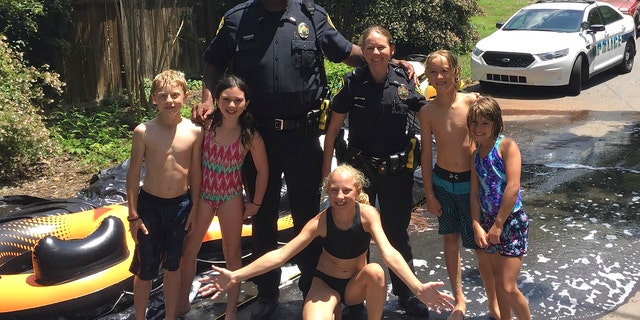A police officer in Asheville, N.C., poses with children playing at a water slide.